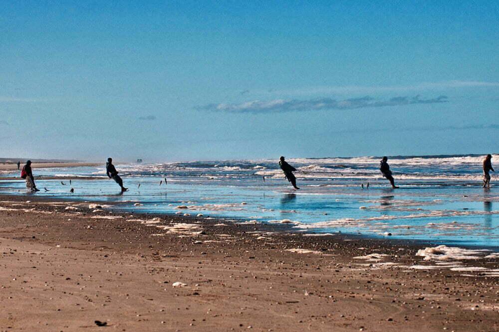 Estação Ecológica do TAIM, imagem de pescadores puxando rede praia do Cassino, RS.