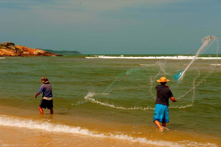 pescadores jogam rede na praia da guarda do embaú